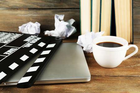 cine: Chapaleta de la película con la computadora portátil y una taza de café sobre fondo de madera