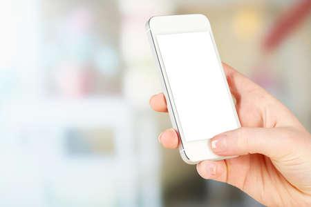 Hand holding smart phone on bright background photo