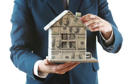 Model of house made of money in male hands isolated on white background photo