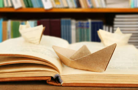 Origami Boats With Old Book On Bookshelves Background Stock Photo