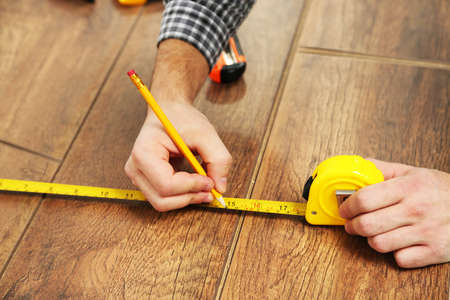 laminate flooring: Carpenter worker installing laminate flooring in the room