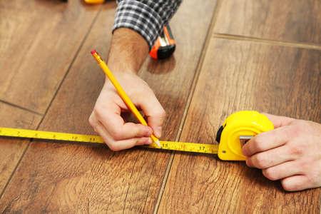 wooden flooring: Carpenter worker installing laminate flooring in the room