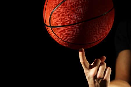 Basketball player holding ball, on dark background photo