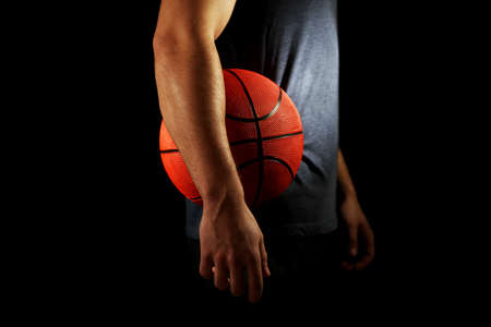 hand basket: Basketball player holding ball, on dark background