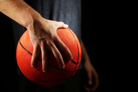 Jugador de baloncesto que sostiene la bola, sobre fondo oscuro