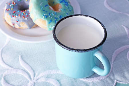 Glazed donuts with cup of milk on white napkin background photo