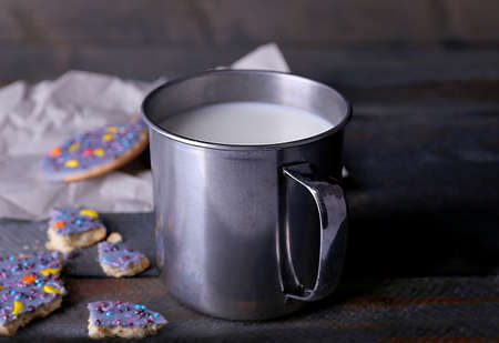crumbled: Crumbled glazed cookies on sheet of paper with metal mug of milk on rustic wooden planks background Stock Photo