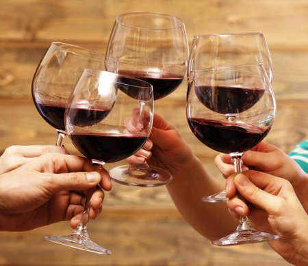 vino: Tintinean los vidrios de vino rojo en las manos sobre fondo de madera r�stico tablones Foto de archivo