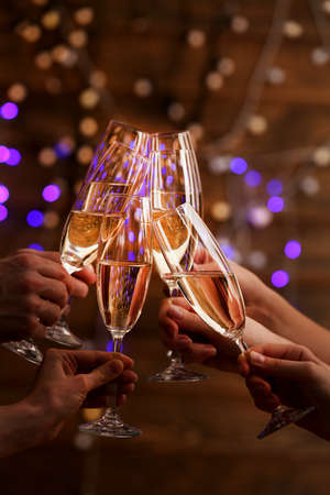 clinking: Clinking glasses of champagne in hands on bright lights background Stock Photo