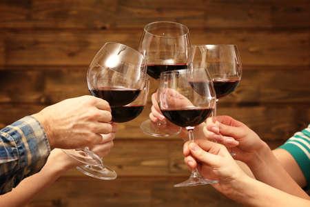 clinking: Tintinean los vidrios de vino rojo en las manos sobre fondo de madera r�stico tablones Foto de archivo