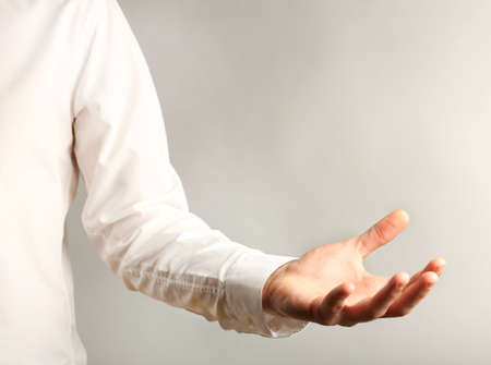 anything: Businessman showing anything on grey background