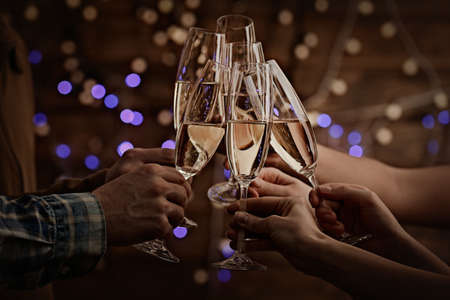 champagne glasses: Clinking glasses of champagne in hands on bright lights background Stock Photo