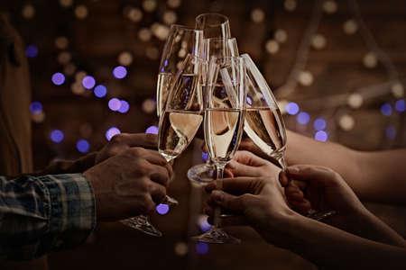 anteojos: Tintineo copas de champán en las manos en las luces brillantes antecedentes Foto de archivo