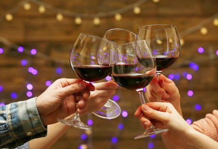 Clinking glasses of red wine in hands on bright lights background Stock Photo - 38149631