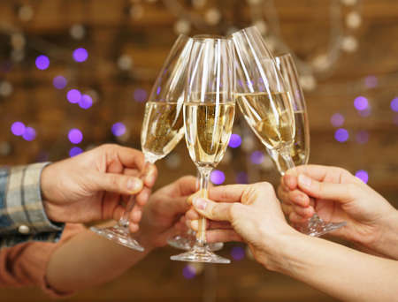 Clinking glasses of champagne in hands on bright lights background Stock Photo