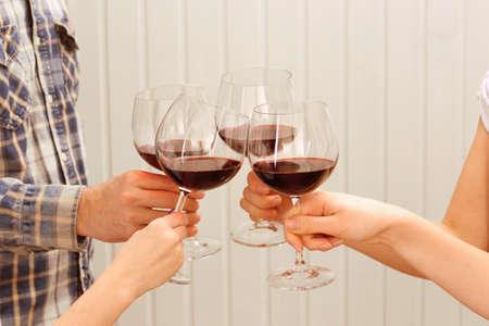 clinking: Clinking glasses of red wine in hands on color wooden planks background Stock Photo