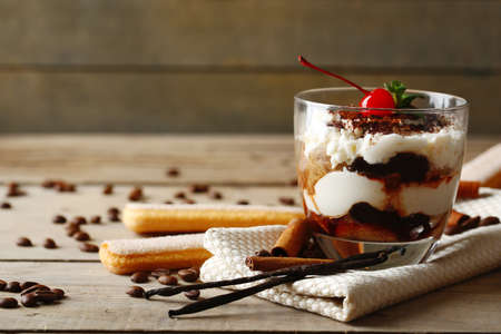 Tasty tiramisu dessert in glass, on napkin, on wooden background