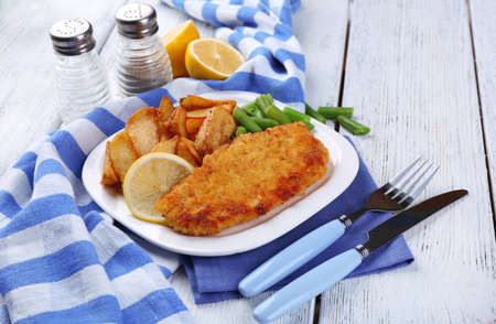 Breaded fried fish fillet and potatoes with asparagus and sliced lemon on plate with napkin on color wooden planks background photo
