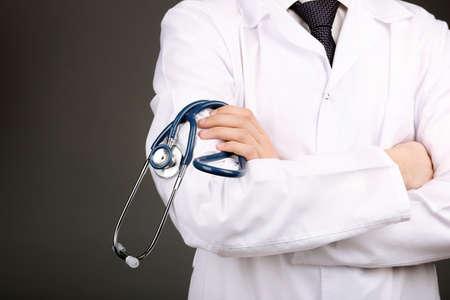 fonendoscopio: Doctor de sexo masculino con el estetoscopio sobre fondo gris
