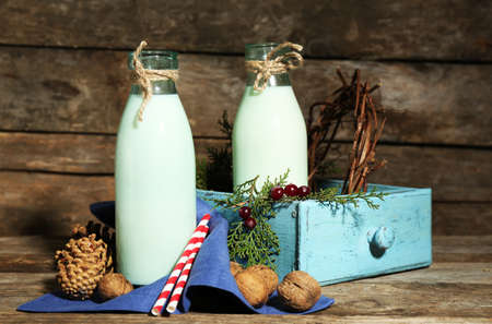 Bottles of fresh milk with natural decor, on wooden background photo