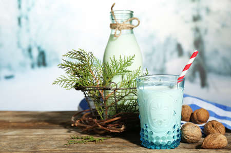 Fresh milk with natural decor, on wooden table, on winter background photo
