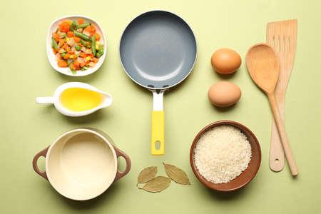 utencilios de cocina: Ingredientes de comida y utensilios de cocina para cocinar en el fondo verde Foto de archivo