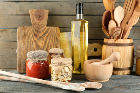 Wooden kitchen utensils with glass bottle of olive oil and canned on wooden planks background photo