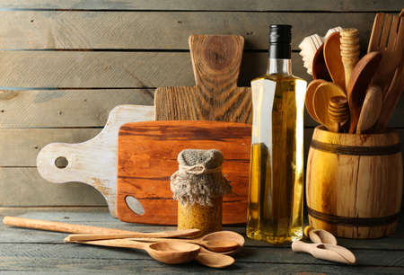 oil tool: Wooden kitchen utensils with glass bottle of olive oil on wooden planks background Stock Photo