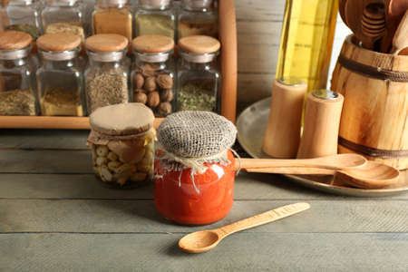 Different spices canned vegetables in glass bottles on stand with utensils and canned on wooden table and planks background photo