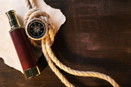 marine: Marine still life spyglass, compass rope and sheet of paper on wooden background