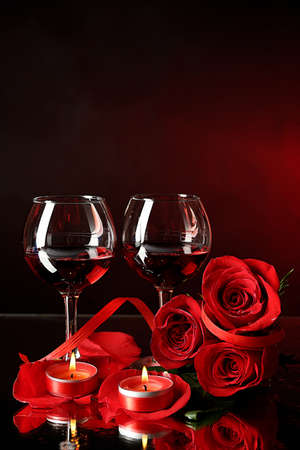 Composition with red wine in glasses, red rose and decorative heart on colorful background photo
