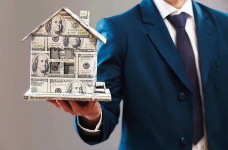 Model of house made of money in male hands on gray background 스톡 콘텐츠