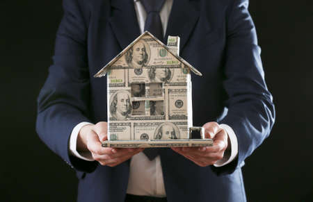 Model of house made of money in male hand, close up photo