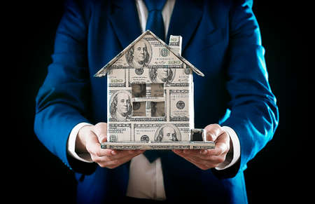 Model of house made of money in male hands on black background photo