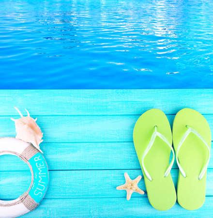 beside: Colored flip flops on wooden platform beside sea