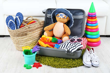 teddy bear baby: Suitcase packed with clothes and child toys on fur rug and white sofa background