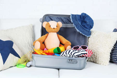Suitcase packed with clothes and child toys on sofa with pillows and white brick wall background photo