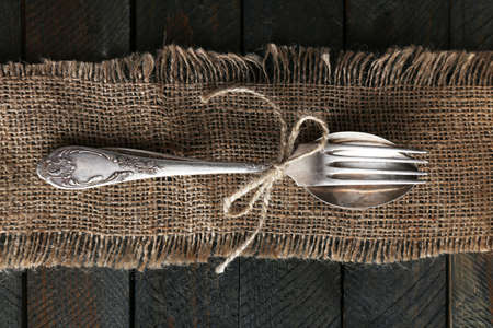Silverware tied with rope on burlap cloth and wooden planks background
