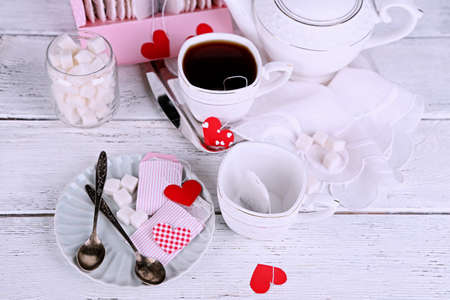 Heart shaped teabag tags, box and teapot on wooden background photo