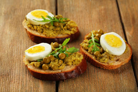 Sandwiches with green peas paste and boiled egg on wooden planks background photo