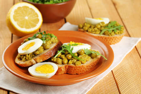 Sandwiches with green peas paste and boiled egg on plate with napkin on wooden planks background photo