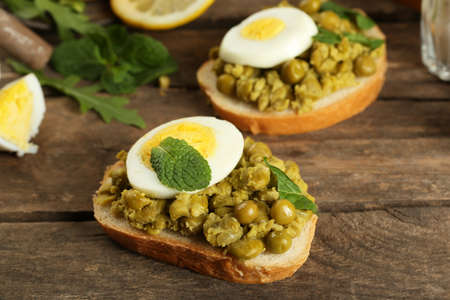 Sandwiches with green peas paste and boiled egg on rustic wooden planks background photo