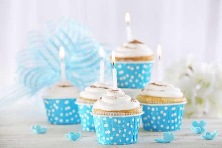 flores de cumpleaños: Magdalenas del cumpleaños deliciosas en la mesa de luz de fondo