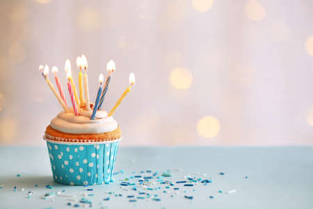 velitas de cumpleaños: Magdalena deliciosa cumpleaños en la mesa sobre fondo claro Foto de archivo