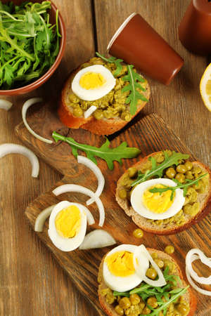 Sandwiches with green peas paste and boiled egg with onion rings and lemon on wooden planks background photo