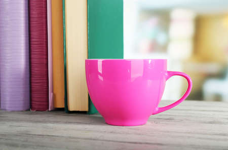 books on a wooden surface: Color cup of drink with books on wooden surface and light background
