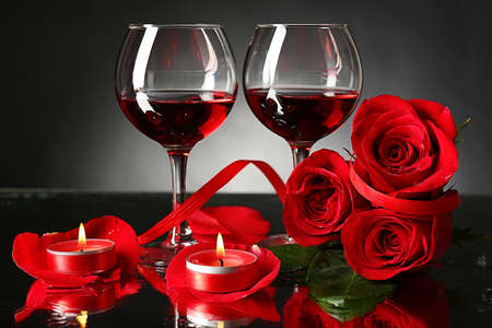Composition with red wine in glasses, red rose and decorative heart on dark background photo