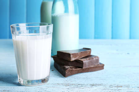 Glass and bottles of milk with chocolate chunks on color wooden planks background photo