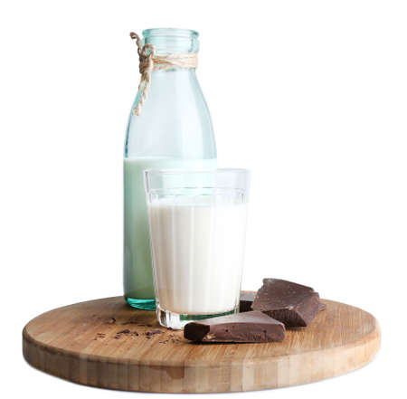 Glass and bottle of milk with chocolate chunks on wooden cutting board isolated on white photo