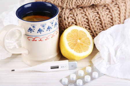 handkerchiefs: Hot tea for colds, pills and handkerchiefs on table close-up